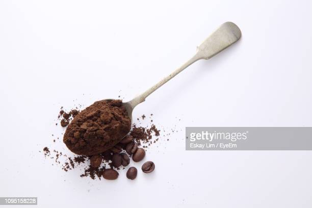 close-up of ground coffee in spoon over white background - café moulu photos et images de collection
