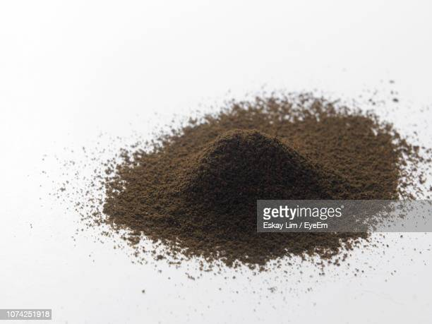 close-up of ground coffee over white background - ground coffee stock photos and pictures