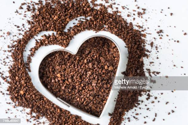 Close-Up Of Ground Coffee With Heart Shape On White Background