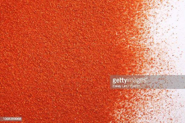 close-up of ground red chili pepper over white background - curry stock pictures, royalty-free photos & images