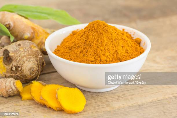 Close-Up Of Ground Turmeric On Wooden Table