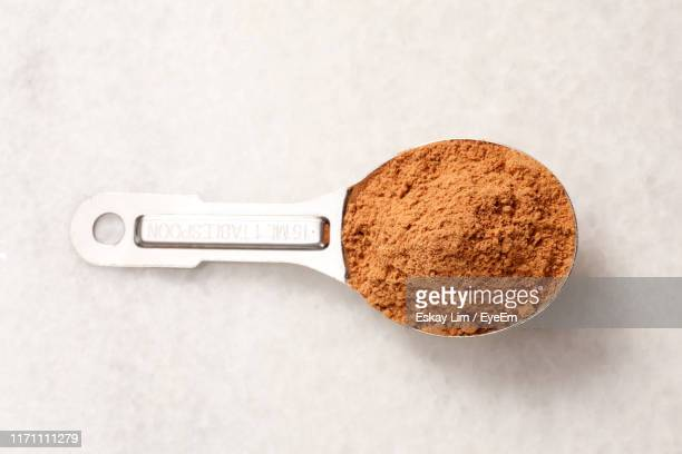 close-up of grounded cinnamon in spoon on table - measuring spoon stock pictures, royalty-free photos & images