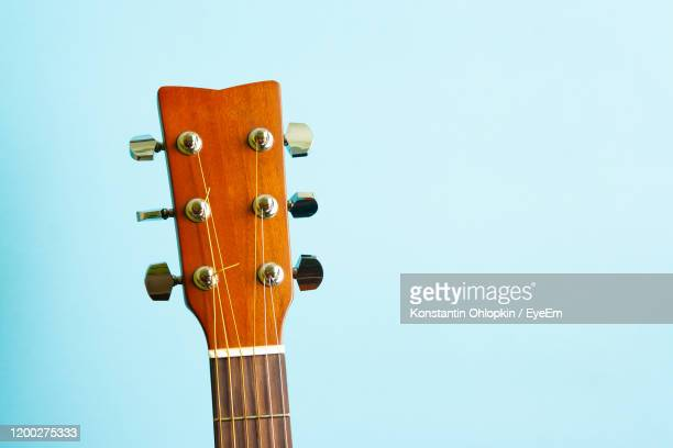 close-up of guitar against blue background - acoustic guitar stock pictures, royalty-free photos & images
