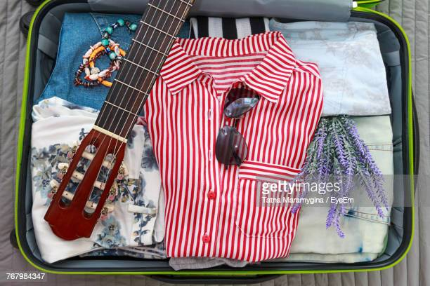 Close-Up Of Guitar And Clothes On Luggage