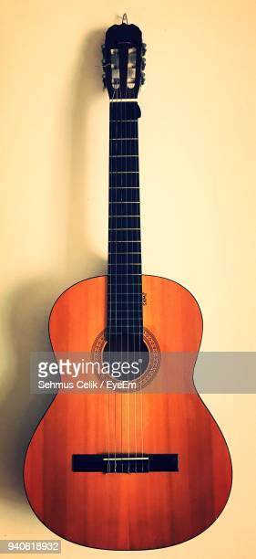 close-up of guitar hanging on wall - acoustic guitar stock pictures, royalty-free photos & images
