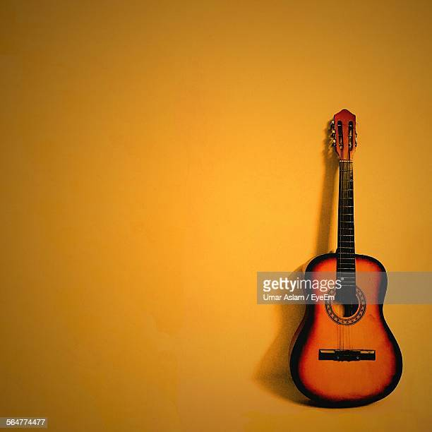 Close-Up Of Guitar With Yellow Background