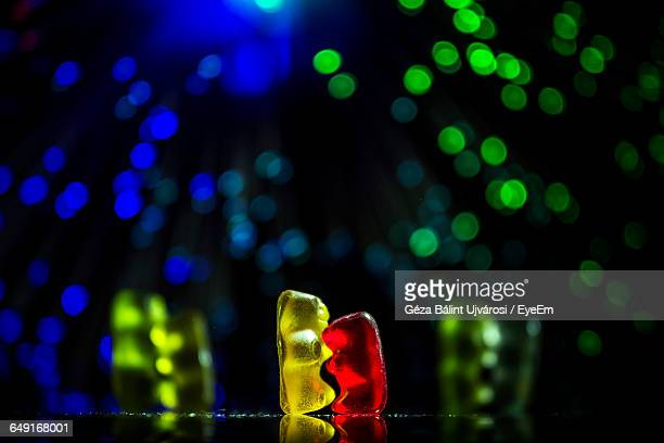 close-up of gummy bears on table against defocused lights - gummi bears stock photos and pictures