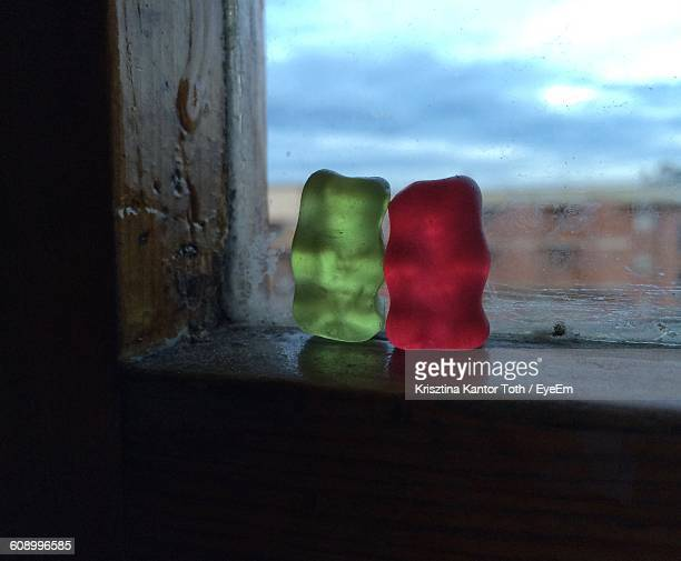 close-up of gummy bears on window - gummi bears stock photos and pictures