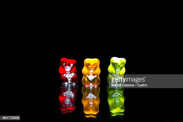 Close-Up Of Gummy Bears With Reflection Against Black Background