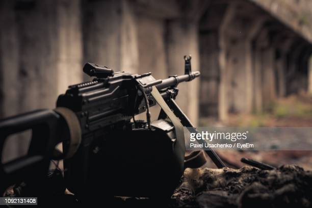 close-up of gun aiming against built structure - machine gun stock pictures, royalty-free photos & images