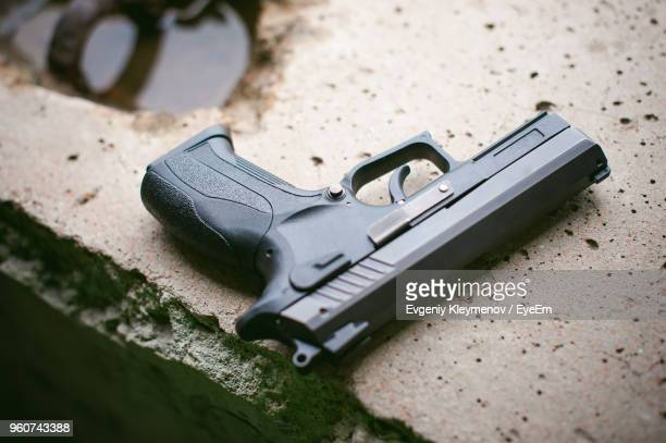 close-up of gun on retaining wall - pistolet photos et images de collection