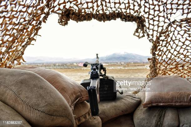 close-up of gun on sacks against clear sky - afghanistan stock pictures, royalty-free photos & images