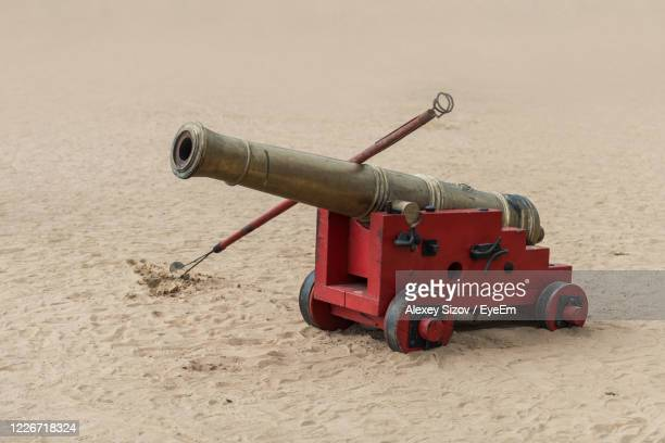close-up of gun on sand - canon stock pictures, royalty-free photos & images