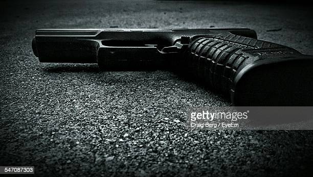 close-up of gun on the ground - guns stock photos and pictures
