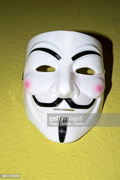 Close-Up Of Guy Fawkes Mask On Yellow Wall