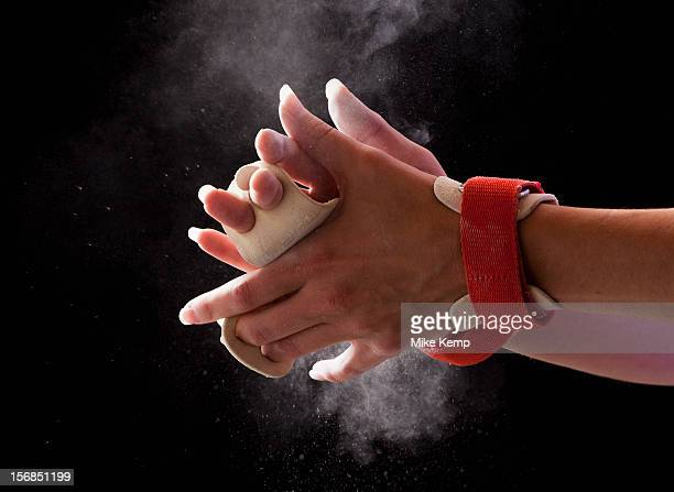 Close-up of gymnast's hands with chalk floating in air around them