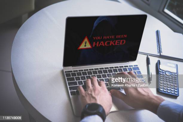 close-up of hacker using laptop on table - サイバー攻撃 ストックフォトと画像