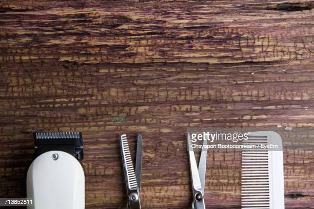 Close-Up Of Hair Clipper With Tools On Wooden Table