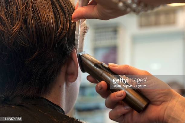 Close-Up Of Hairdresser Cutting Hair Of Man