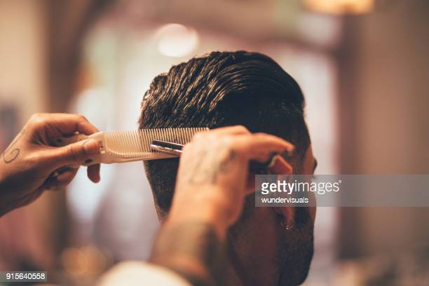 Close-up of hairstylist's hands cutting strand of man's hair