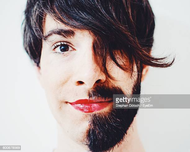 Close-Up Of Half Bearded Man With Lipstick Against White Background