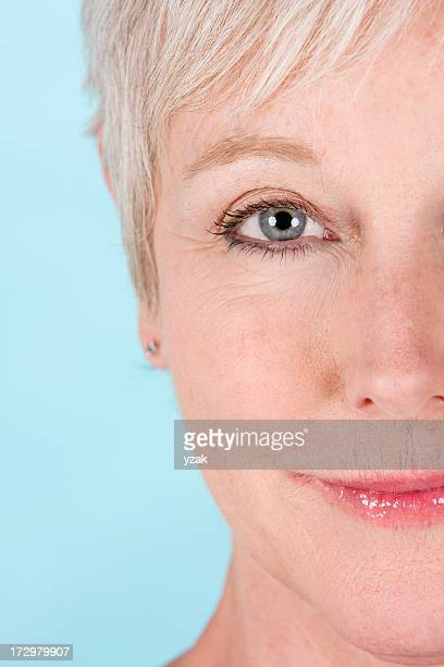 A close-up of half the face of a blonde and blue-eyed woman