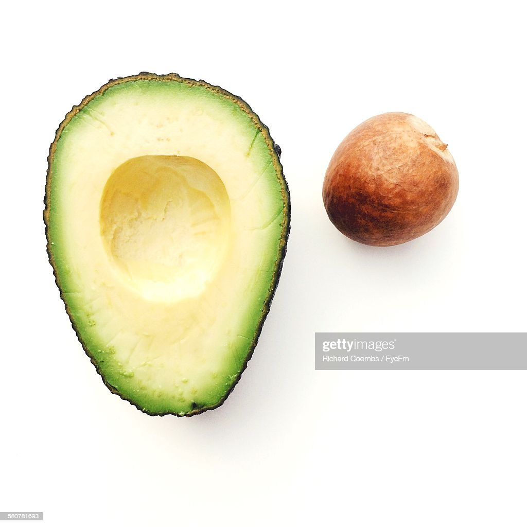 Close-Up Of Halved Avocado With Seed Against White Background : Stock-Foto