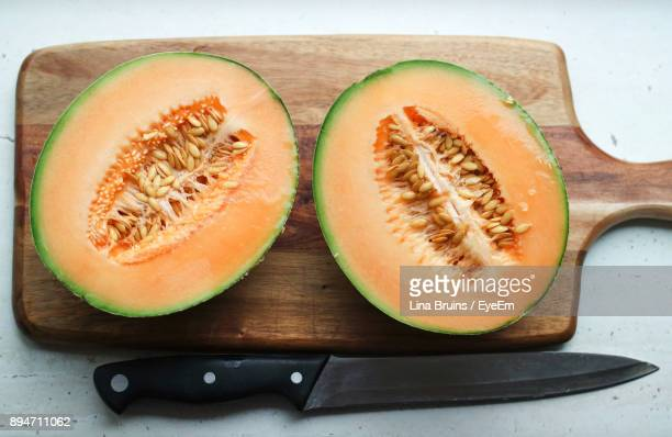 Close-Up Of Halved Cantaloupe Melon On Cutting Board
