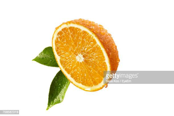 Close-Up Of Halved Orange Fruit Over White Background