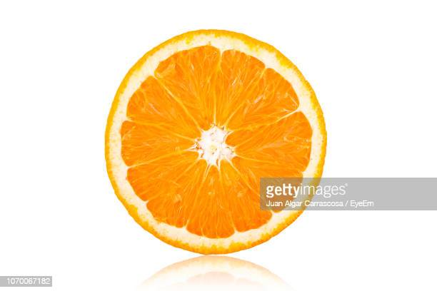 close-up of halved orange over white background - arancione foto e immagini stock