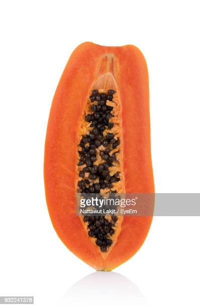 close-up of halved papaya over white background - papaya stock photos and pictures