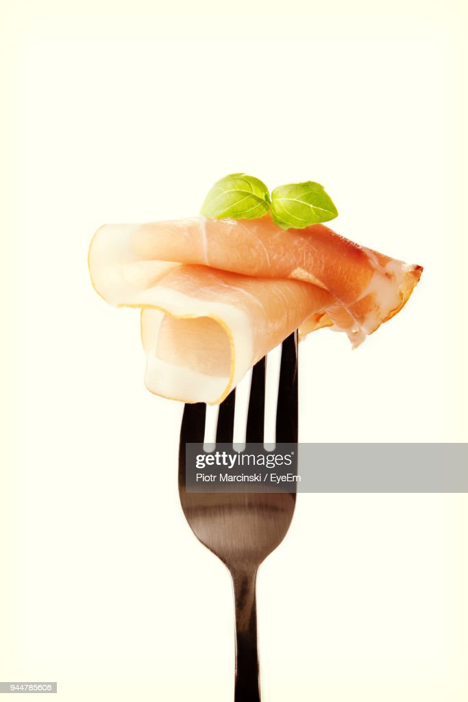 Close-Up Of Ham And Basil Leaf On Fork Against White Background : Stock Photo