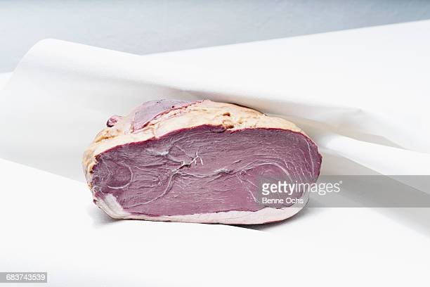 Close-up of ham on white napkin at table