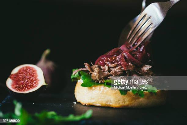Close-Up Of Hamburger With Fig On Table Against Black Background