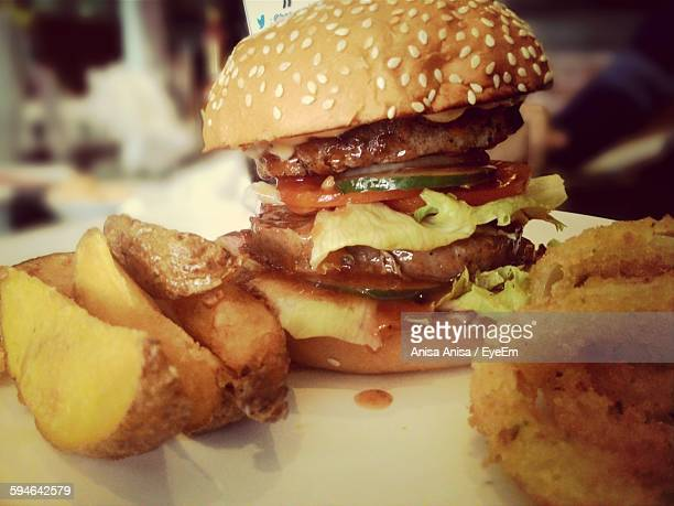 Close-Up Of Hamburger With Fried Onions And Potatoes Served On Table