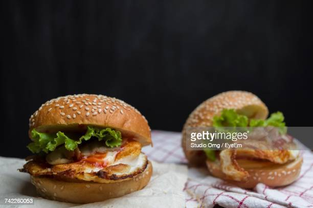 Close-Up Of Hamburgers On Napkin Against Black Background