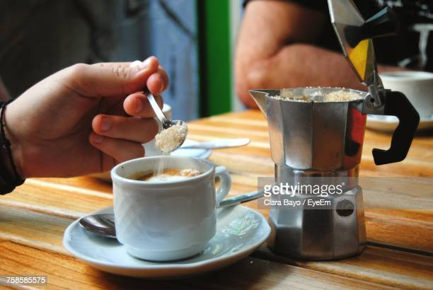 close-up of hand adding sugar to coffee on table - sugar coffee stock photos and pictures