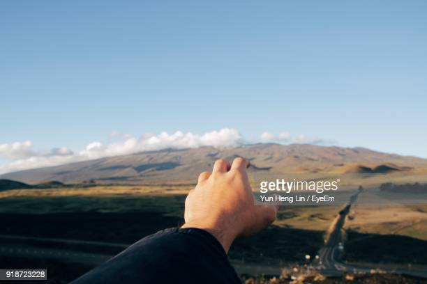 Close-Up Of Hand Against Mountain