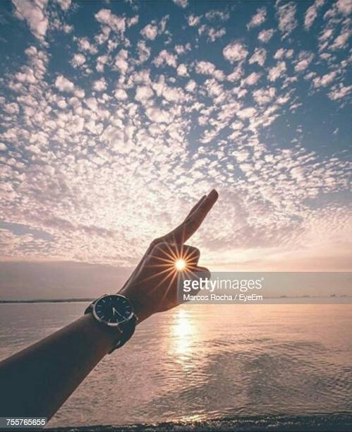 Close-Up Of Hand Against Sea At Sunset