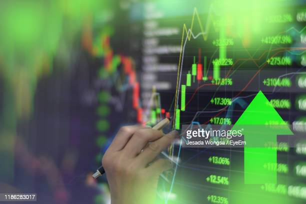 close-up of hand analyzing stock market data on screen - börse stock-fotos und bilder