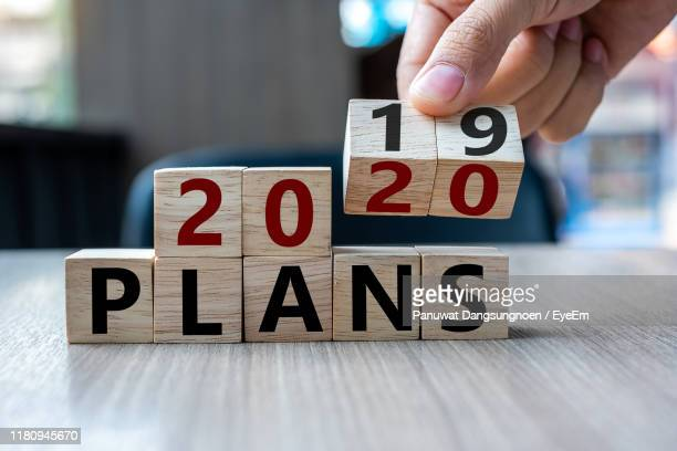 close-up of hand arranging toy blocks on table - 2020 calendar stock photos and pictures