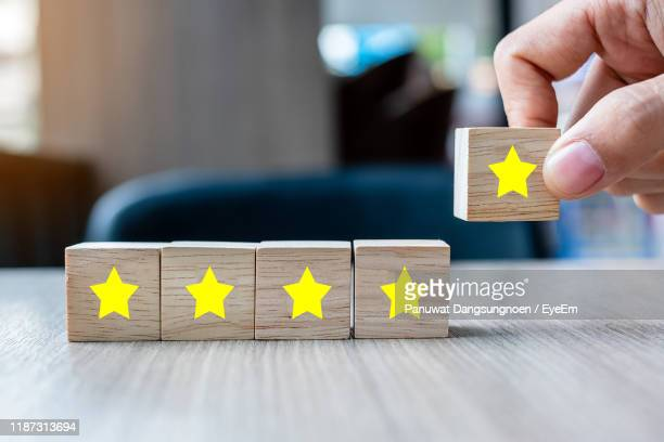 close-up of hand arranging toy blocks with star shapes on table - rating stock pictures, royalty-free photos & images