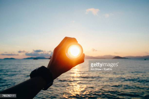 close-up of hand at sunset - zonnestraal stockfoto's en -beelden