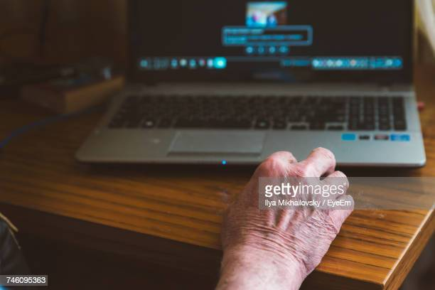 Close-Up Of Hand By Laptop