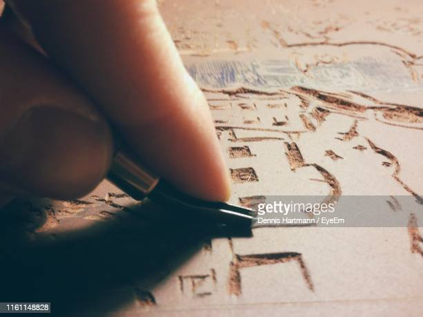 close-up of hand carving with tool on wood - lino stock pictures, royalty-free photos & images