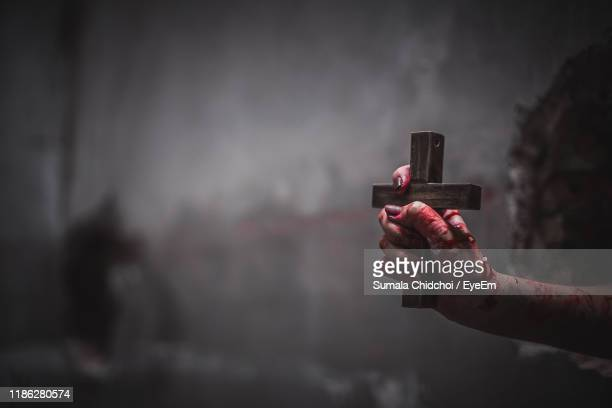 close-up of hand covered with blood holding crucifix - crucifixion photos et images de collection