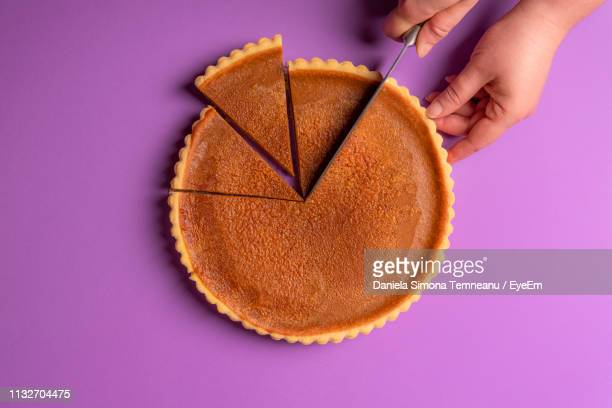 close-up of hand cutting pastry on purple background - パイ ストックフォトと画像