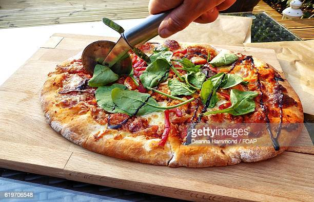 Close-up of hand cutting pizza with pizza cutter