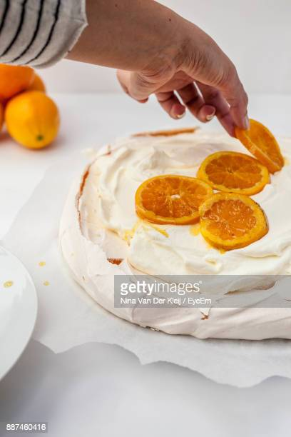Close-Up Of Hand Decorating Ice Cream With Orange Slices On Table