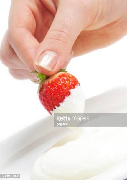 close-up of hand dipping strawberry in cream over white background - sahne stock-fotos und bilder